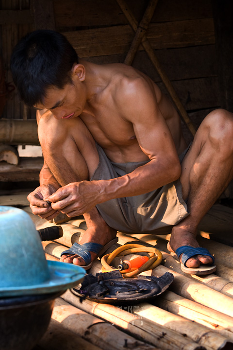 Hill tribe man doing repairs