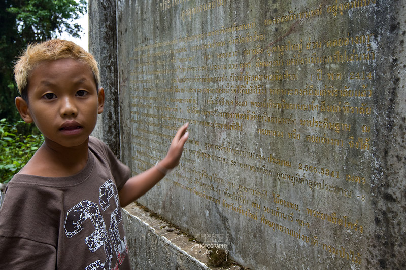 Thai boy reading stone tablet at the peak