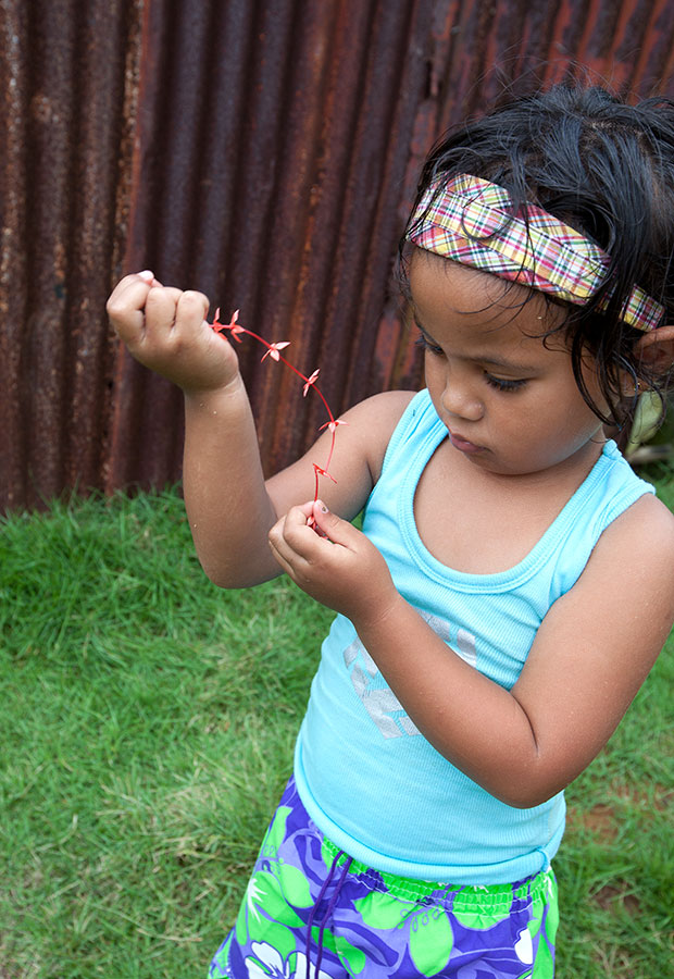 3 1/2 year old girl strings together flowers for a necklace. Pohnpei, FSM IMG_7604.jpg