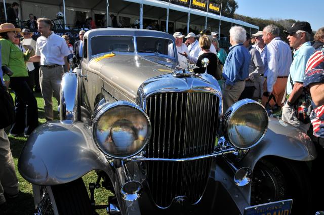 Helen Nethercutt talks to fellow car collector Bruce Meyer, rear left, behind 1933 Duesenberg SJ Arlington Torpedo Sedan