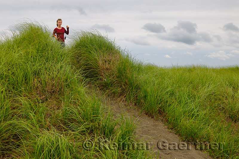 Girl tourist on Port Maitland beach sand dunes with grass Nova Scotia