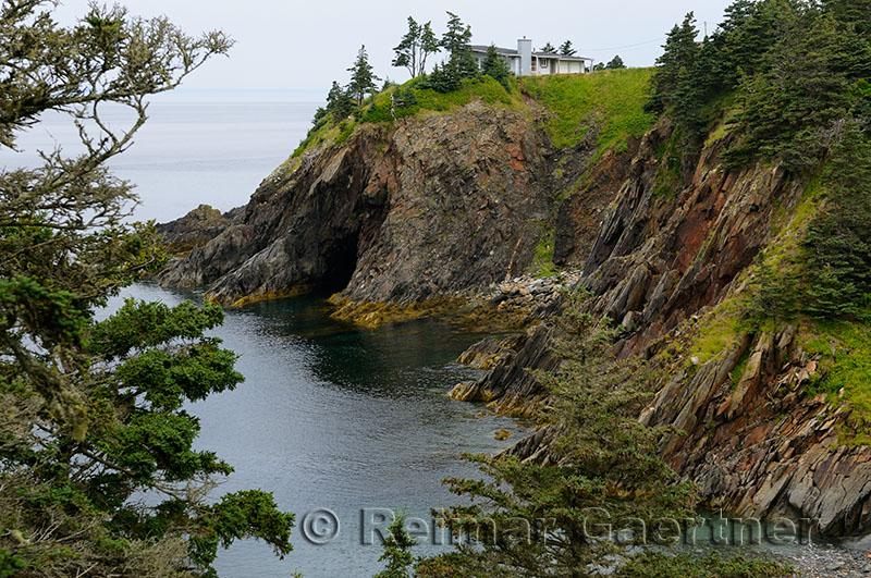 House above the sea cliffs and cave of Smugglers Cove Provincial Park Nova Scotia