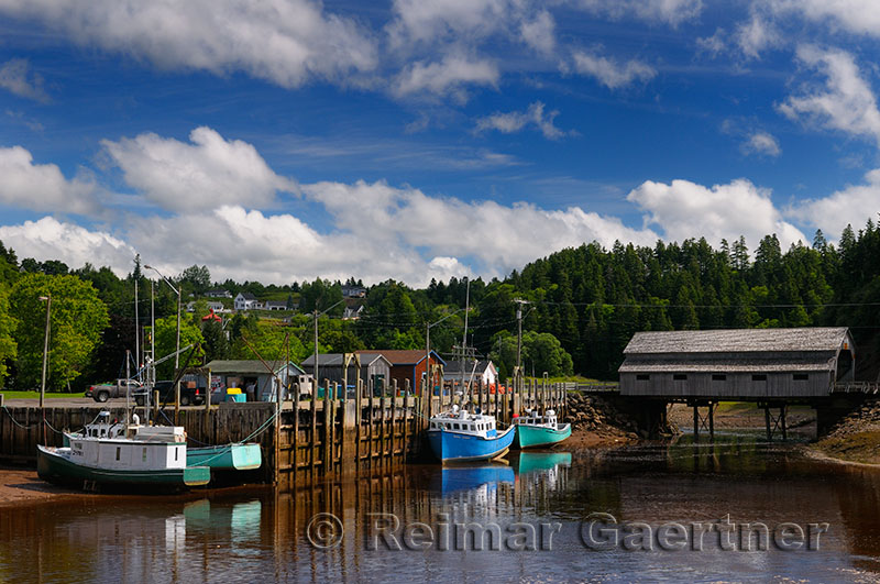 Covered bridge and wharf with boats at low tide in St Martins New Brunswick