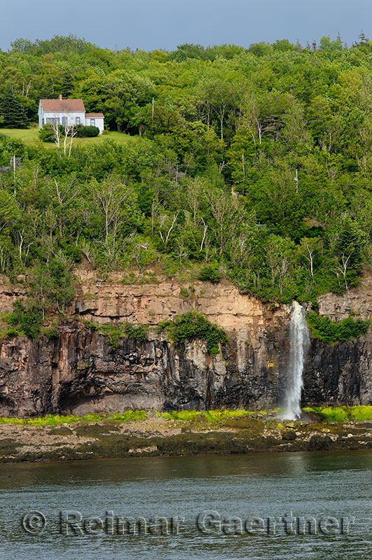 Lone house above waterfalls at Digby Gut on the North Peninsula of Annapois Basin Nova Scotia