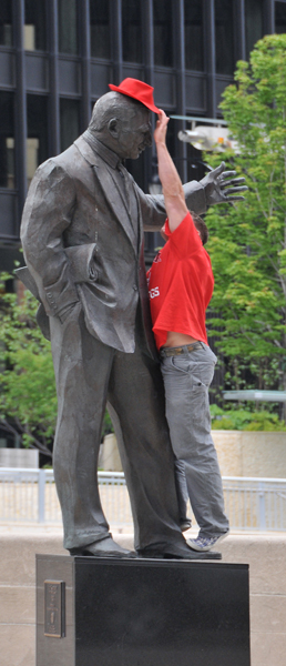 Removing his red hat from statue