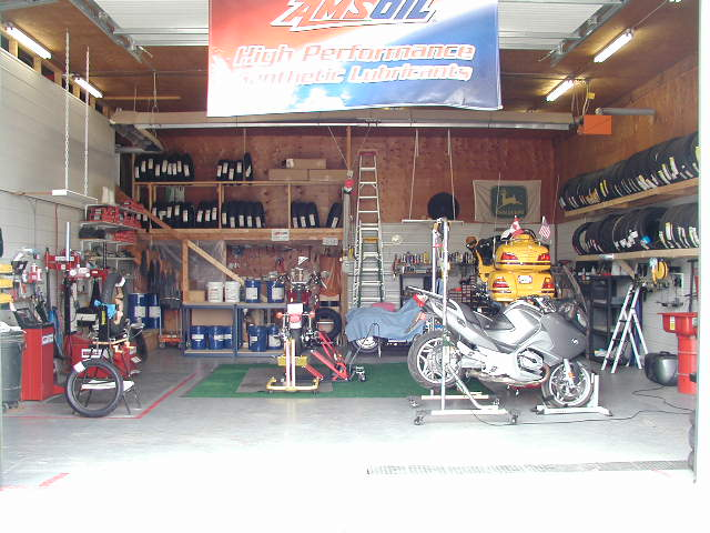 Entrance into the new shop area will be through the wall  where the white steel is infront of the Yellow bike on the lift..JPG