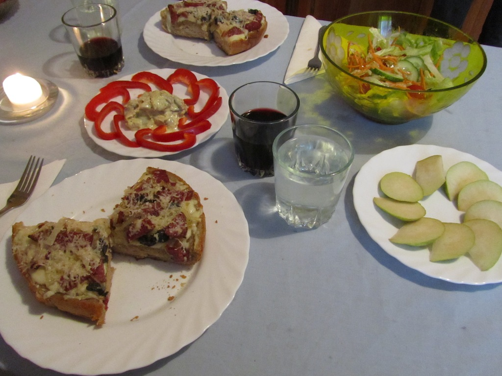 black olive & sausage pizza, herring with cream & peppers, salad, and apple