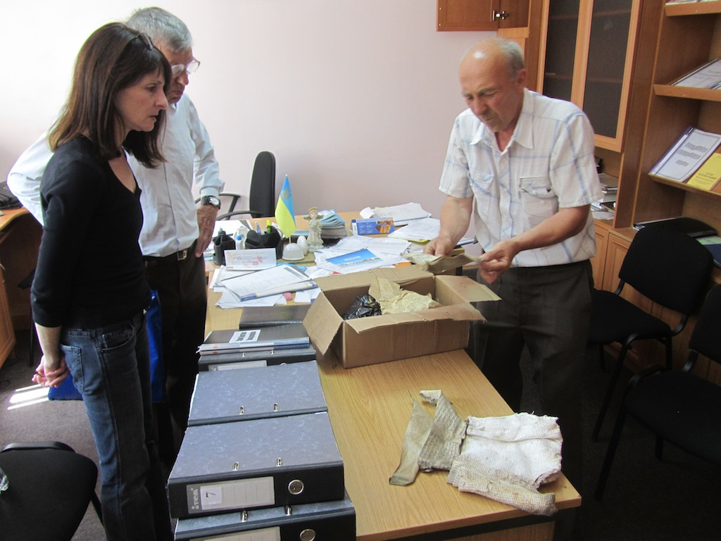 the director of a local school shows us papers found in the former Jewish community buildings on the school site