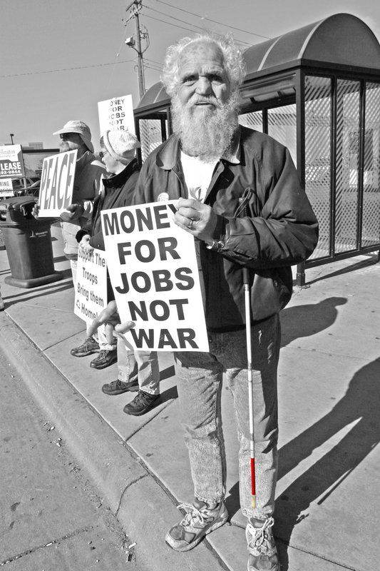 Man with red tipped cane and sign money for jobs not for war