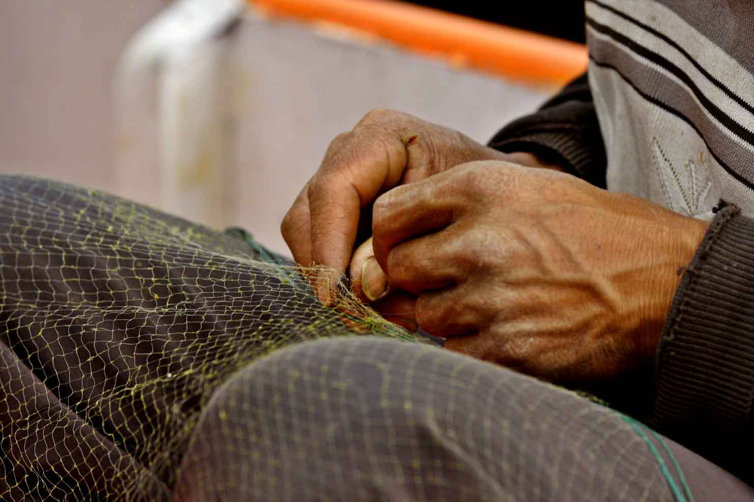 Hands of Bai fisherman repairing gill net. Dali, China. .jpg