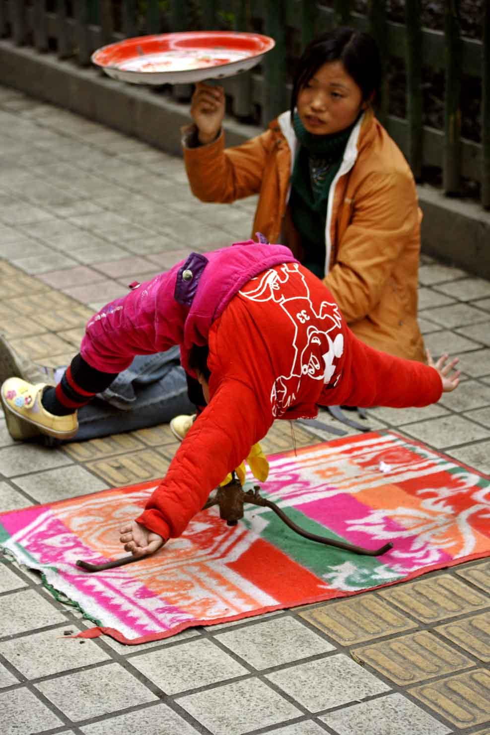 Girl spinning while balancing on mouth. Jishou City, China.