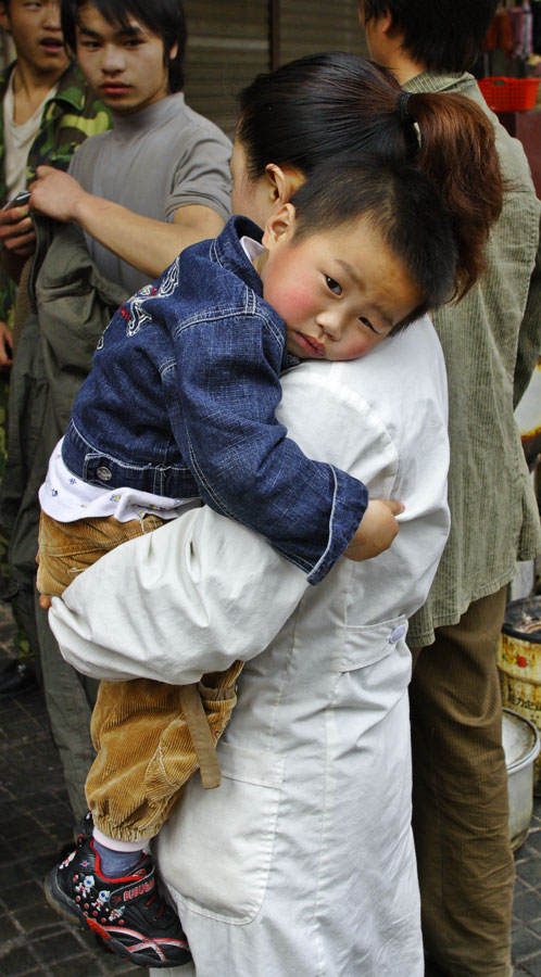Child being held by mother. Jishou City, China