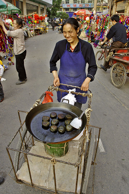 Selling glutinous (sticky) rice with Artemisia (sage). Street market.