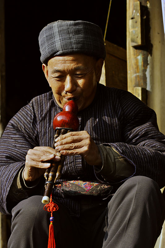 A master playing a Hmong traditional gourd instrument.