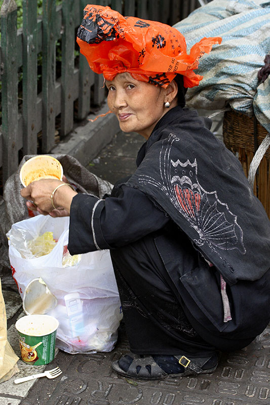 Sifting through the garbage, a plastic bag against the rain and Smiling.