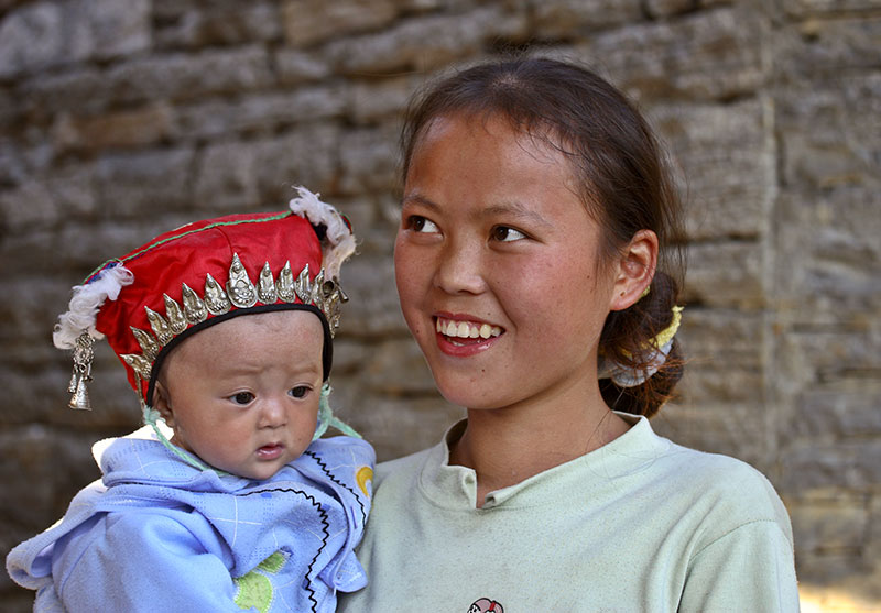 Young mother and child with traditional Miao headwear.