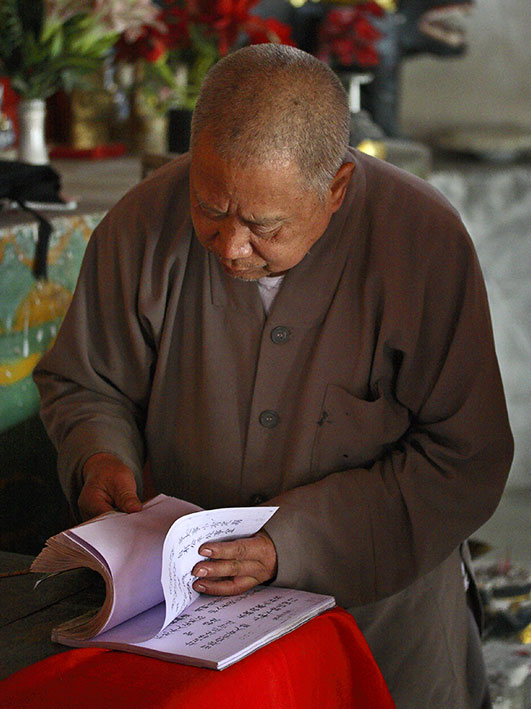 Buddhist monk using a reference book for fortunes.