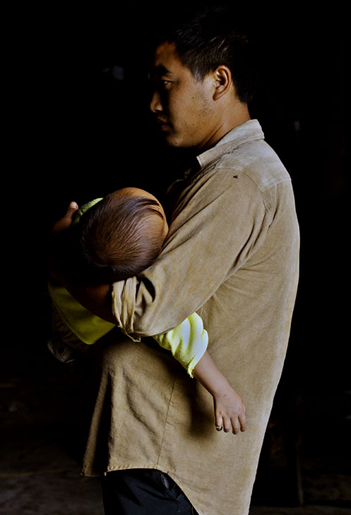 Father and sleeping child. Remote village China. 2006