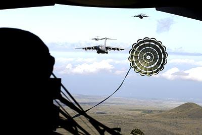 USAF C-17 Globemaster III extraction chute opens over the drop zone