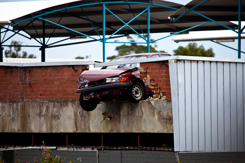 Car ploughs through rooftop carpark wall