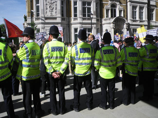 Standing Behind the Row of Policemen