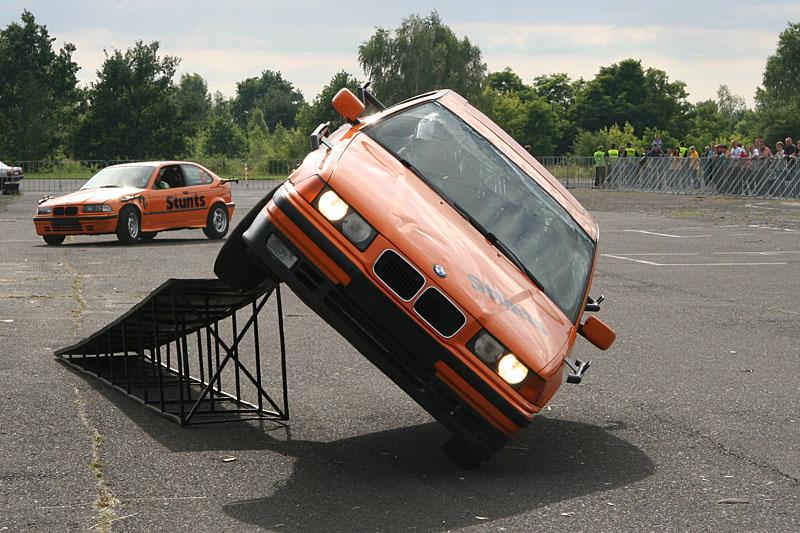 Girls inside stunts car on two wheels drive
