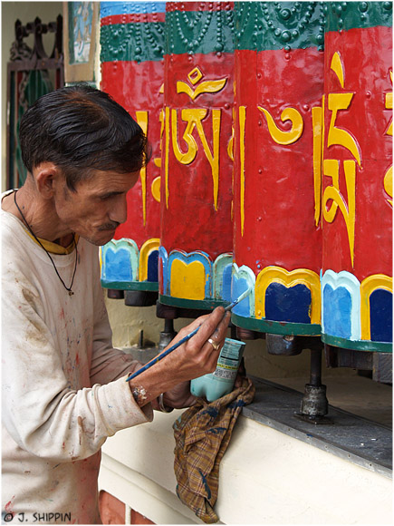 A man painting Tibetan prayer wheels, in the town which the Dalai Lama stays at; Mcleod-Ganj.