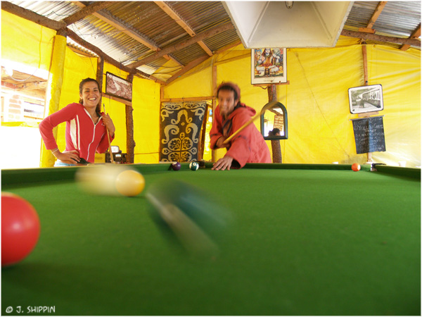 Tourists playing pool in the Guest House