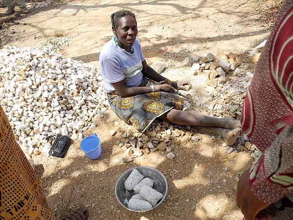 Now stones are taken from the former gold mine and are cut into pieces, Laongo, Burkina Faso