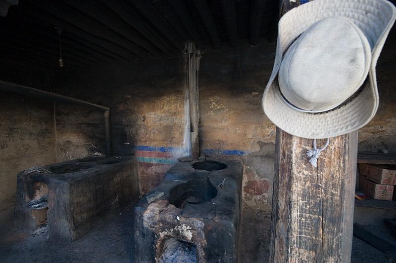 Tibetan cowboy hat hanging outside a kitchen.