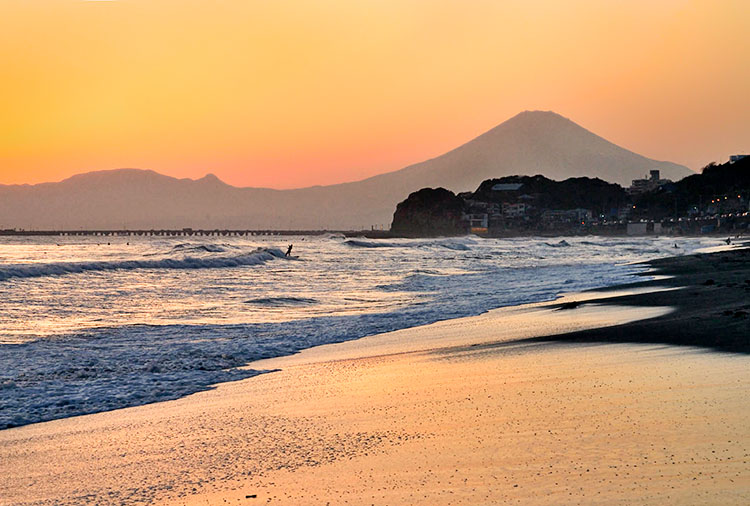 Surfer at Kamakura with Mount Fuji in the background
