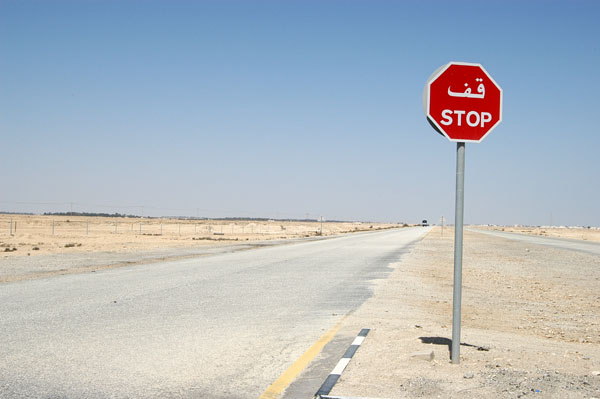 Stop sign on the road to Al Zubara through the desert of northern Qatar