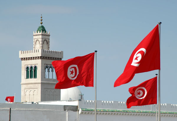 Tunisian flags flying over Place de la Kasbah with the minaret of the Kasbah Mosque