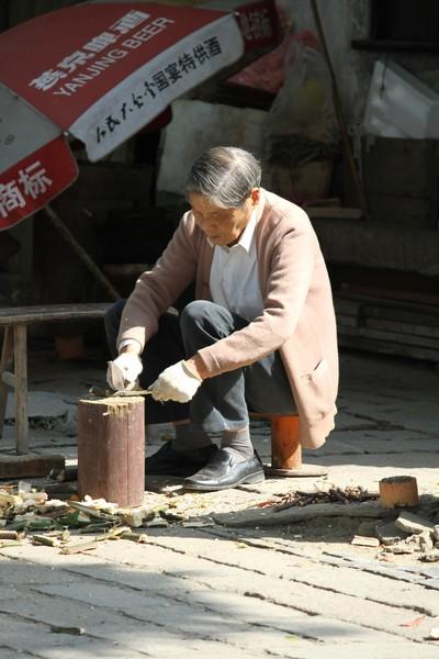 Old man chopping kindling