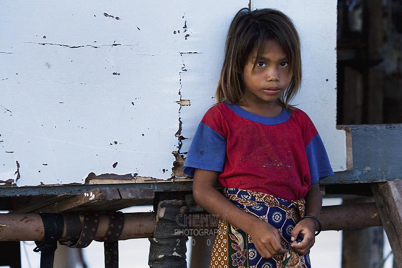 Sea gypsy girl outside her home