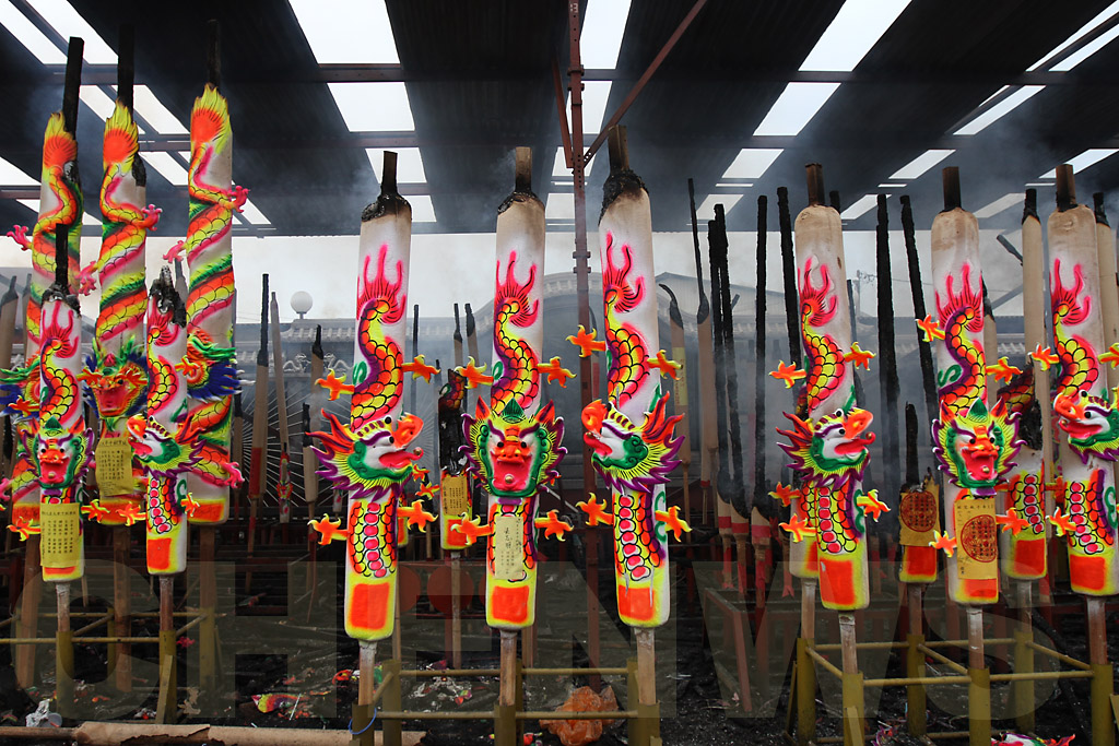 Giant joss-sticks with dragon ornaments and motifs burn outside the temple courtyard.