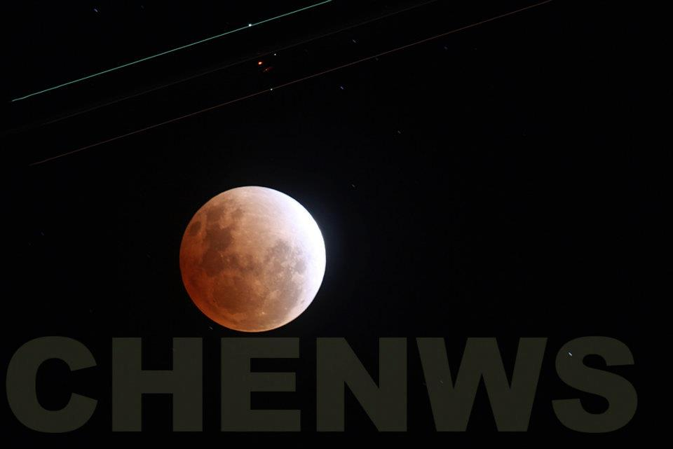 Plane flying over a full lunar eclipse (the streaks of light came from the planes wingtips)  on the night of 11 Dec 2011