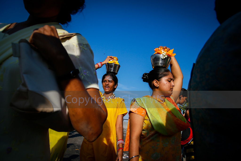 Devotees carry milk pot on their heads walk to the temple