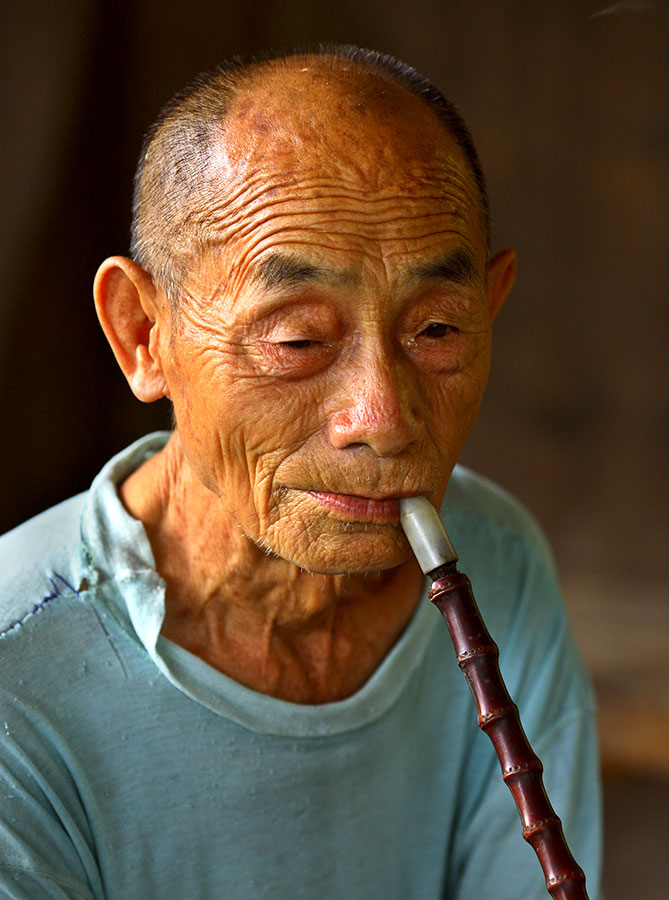 3681 Kam elder smoking a traditional bamboo pipe with ceramic bowl.