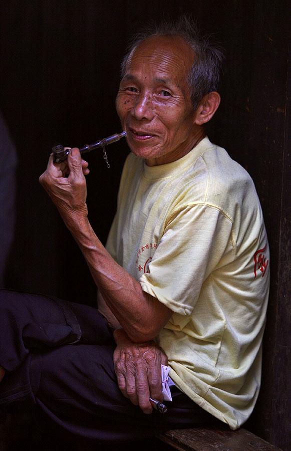 4417 Kam elder relaxing and smoking his pipe.