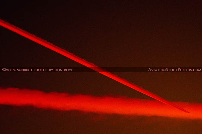 2012 - unknown four-engine airliner leaving a sunlit contrail as it flies in front of another contrail stock photo #2474