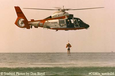 Late 80s - USCG HH-65 #6525 hoisting Coast Guard Reserve air crew member during wet drill
