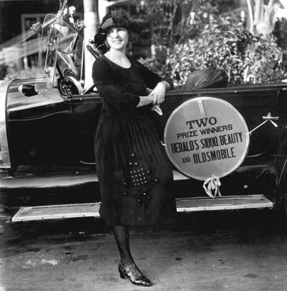 1922 - Beauty prize winner standing by an Oldsmobile on Miami Beach