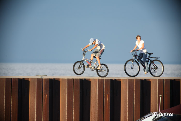 two kids riding on the seawall