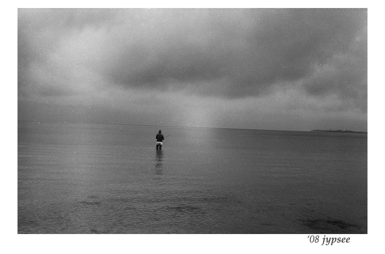 fisher on a glassy san carlos bay under a big gray sky
