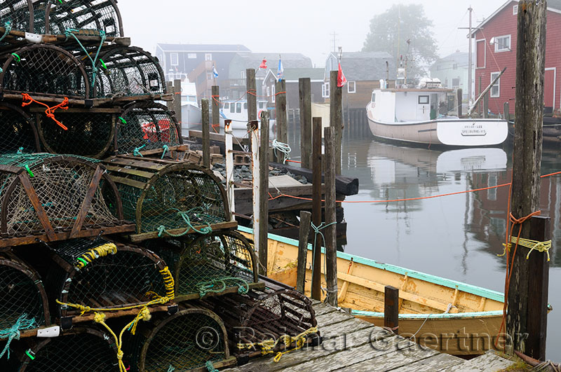 Wood lobster traps on dock and boats in fog at Fishermans Cove Eastern Passage Halifax Nova Scotia