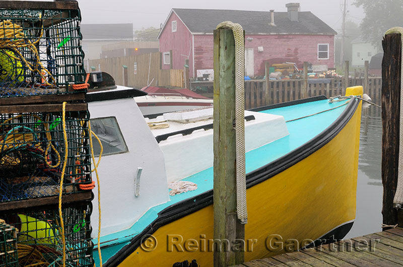 Lobster traps with yellow boat and red house in fog at Fishermans Cove Eastern Passage Halifax Nova Scotia
