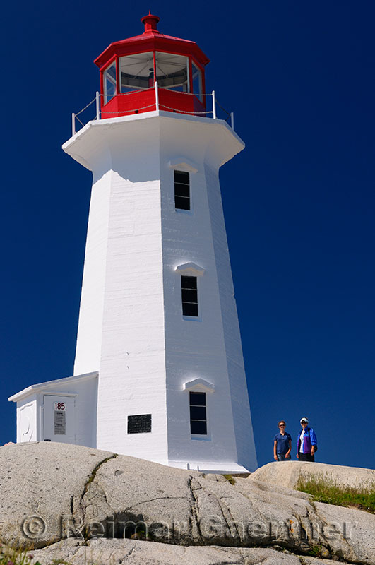 Peggys Cove lighthouse against a blue sky with mother and daughter tourists