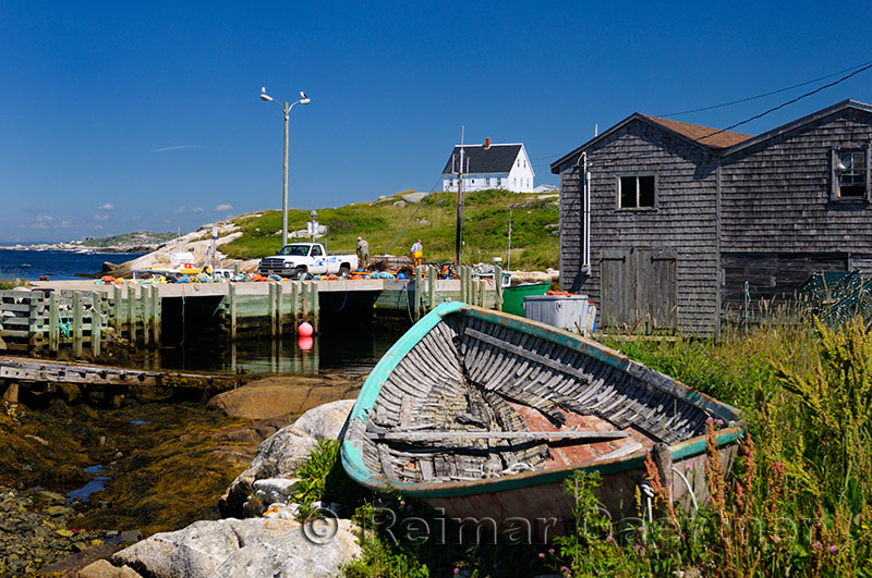 Working fishermen on the dock at Peggys Cove Nova Scotia with abandoned boat