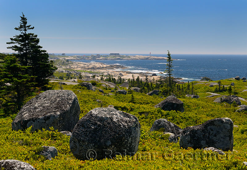 Glacial boulders and rocky coastline at Whalesback with Peggys Cove in distance